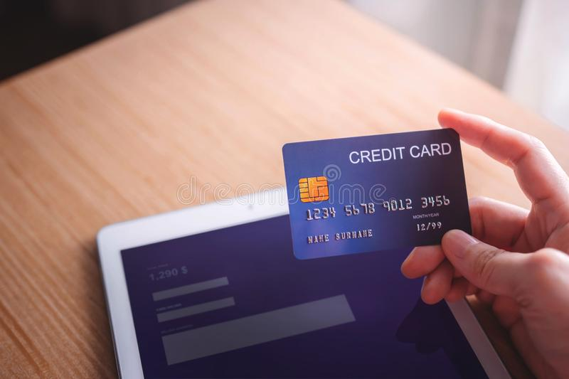 Cliente de la mujer joven que usa la tarjeta y la tableta de crédito al pago en línea fotografía de archivo