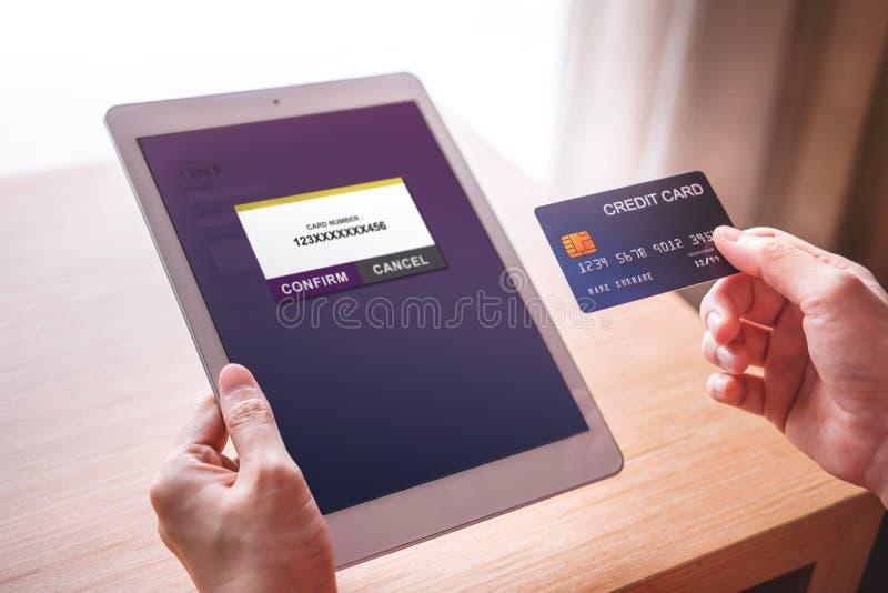 Cliente de la mujer joven que usa la tarjeta y la tableta de crédito al pago en línea fotografía de archivo libre de regalías