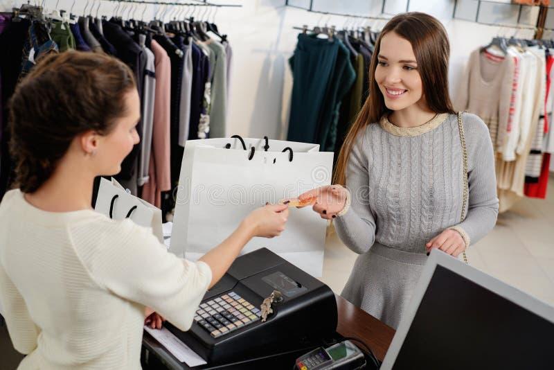 Cliente de la mujer que paga con la tarjeta de crédito en la sala de exposición foto de archivo libre de regalías