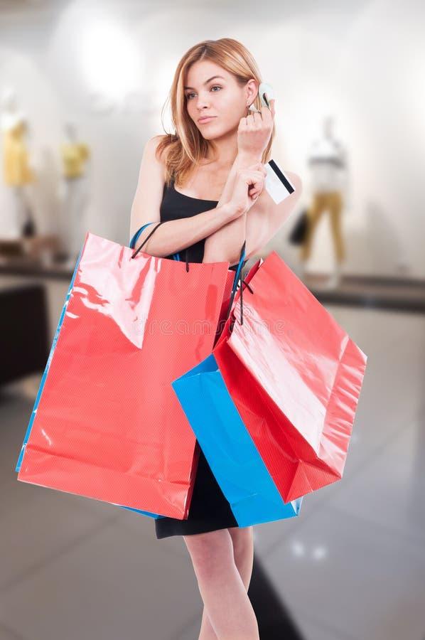 Cliente de la mujer que paga con la tarjeta y el dinero de crédito imagen de archivo libre de regalías