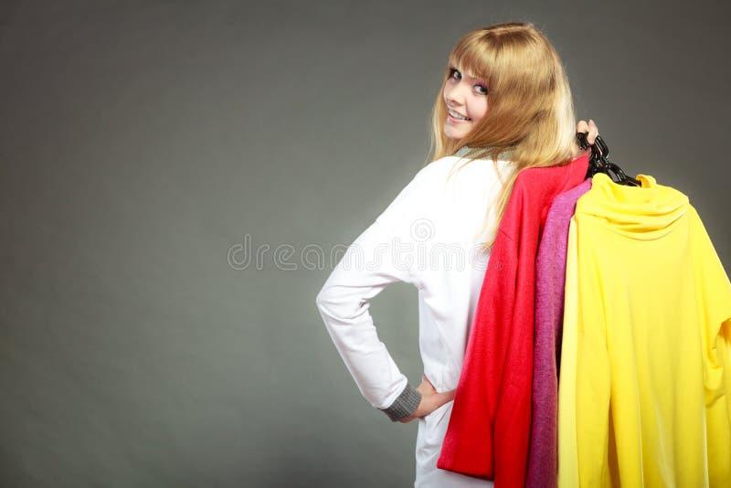 Cliente de la mujer que sostiene suspensiones con ropa fotos de archivo libres de regalías
