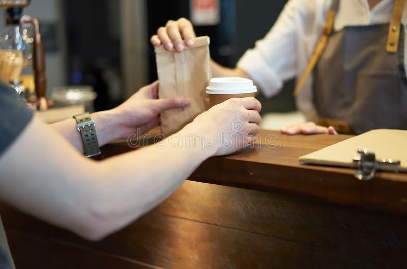 Cliente de la porción de Barista en la cafetería Estafa del Takeaway y del servicio foto de archivo