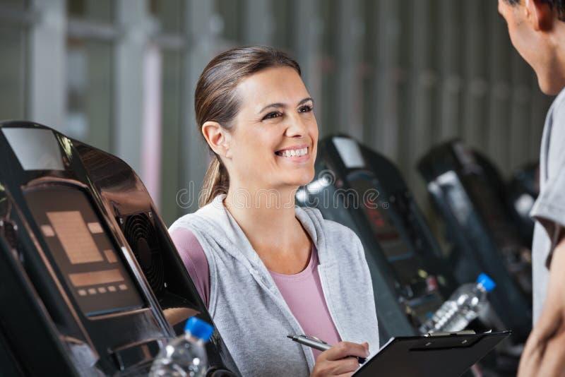 Cliente de Looking At Male do instrutor que exercita sobre foto de stock