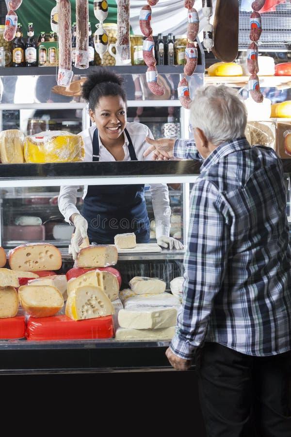 Cliente de Taking Order From de la dependienta en la tienda del queso fotografía de archivo libre de regalías