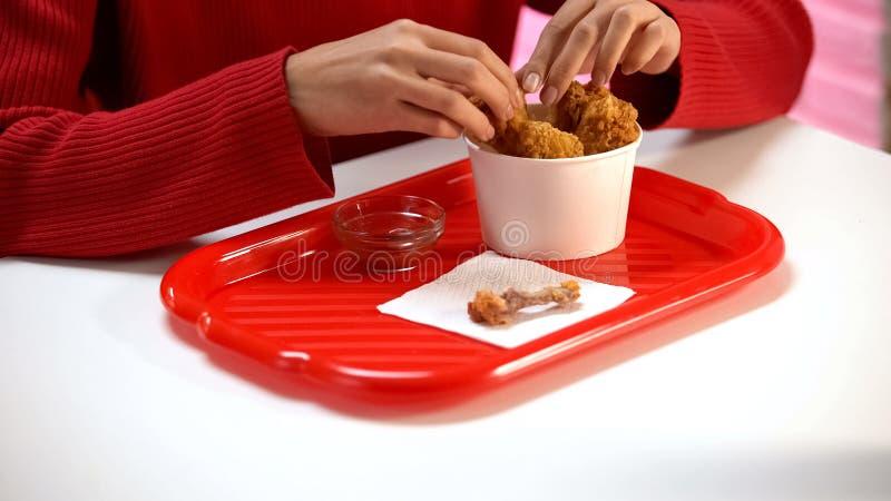 Cliente dei bistrot che mangia le ali di pollo croccanti, ossa che si trovano sulla tavola, alimento fotografie stock libere da diritti