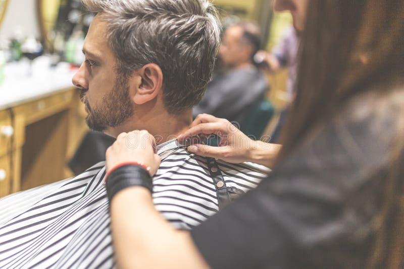 Cliente dei pantaloni a vita bassa coperto di taglio di capelli aspettante del capo fotografia stock libera da diritti