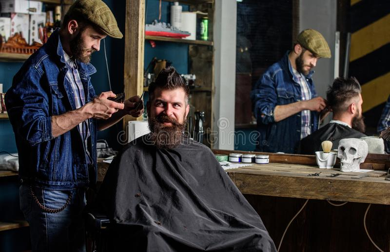 Cliente dei pantaloni a vita bassa e del barbiere con la barba che controlla taglio di capelli in specchio, fondo scuro L'uomo co fotografia stock