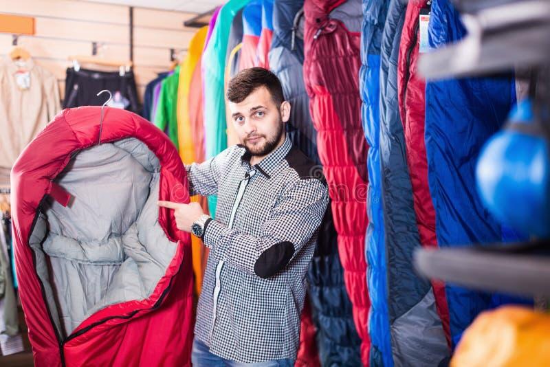 Cliente del hombre joven que elige el nuevo saco de dormir en tienda foto de archivo libre de regalías