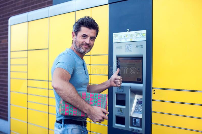 Cliente del hombre que usa la máquina terminal automatizada de los posts del servicio del uno mismo o foto de archivo