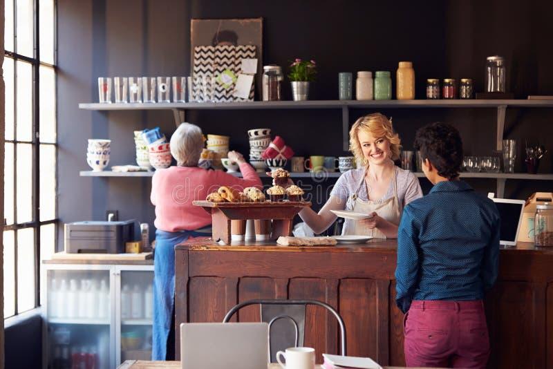 Cliente del servizio del personale in caffetteria occupata fotografie stock libere da diritti