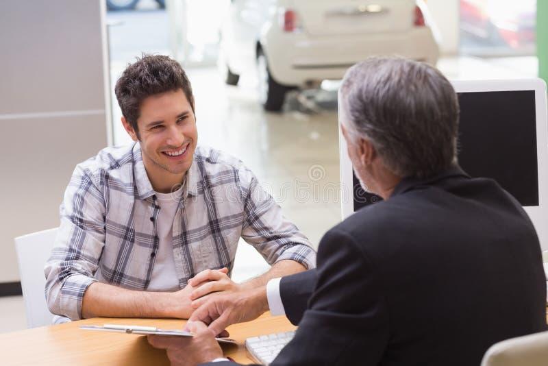 A cliente del vendedor mostrando donde firmar el trato fotos de archivo libres de regalías