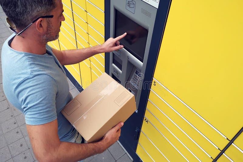 Cliente dell'uomo che per mezzo della macchina o dell'armadio automatizzata del terminale della posta di self service per deposit fotografia stock