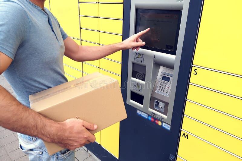 Cliente dell'uomo che per mezzo della macchina o dell'armadio automatizzata del terminale della posta di self service per deposit fotografie stock libere da diritti