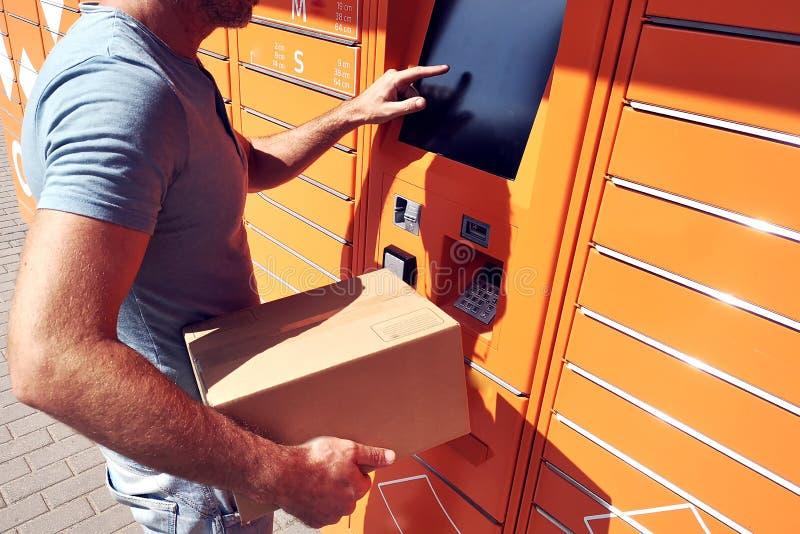 Cliente dell'uomo che per mezzo della macchina o dell'armadio automatizzata del terminale della posta di self service per deposit immagini stock