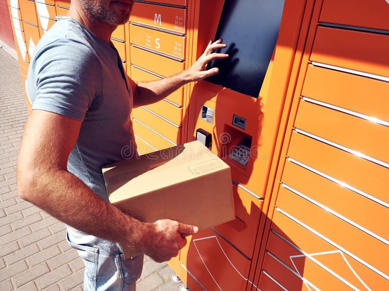 Cliente dell'uomo che per mezzo della macchina o dell'armadio automatizzata del terminale della posta di self service per deposit fotografie stock