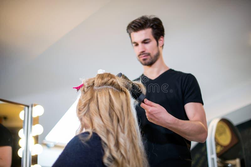 Cliente della bionda e del parrucchiere fotografie stock