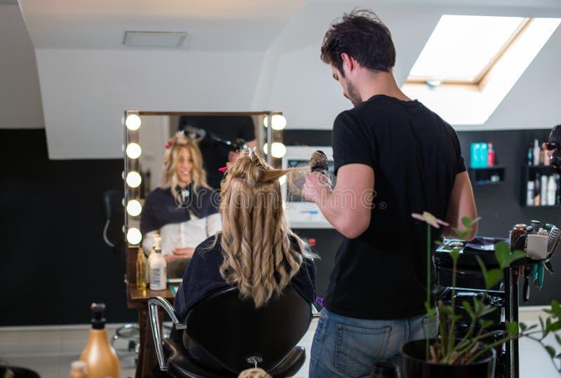 Cliente della bionda e del parrucchiere al salone fotografia stock libera da diritti