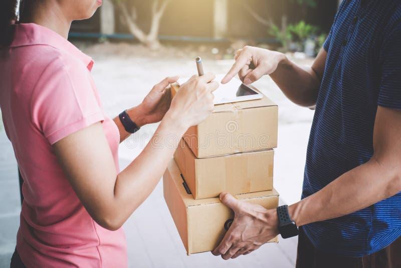 Cliente della donna che aggiunge firma in compressa digitale e che riceve un pacchetto delle scatole di cartone dal corriere di s fotografia stock
