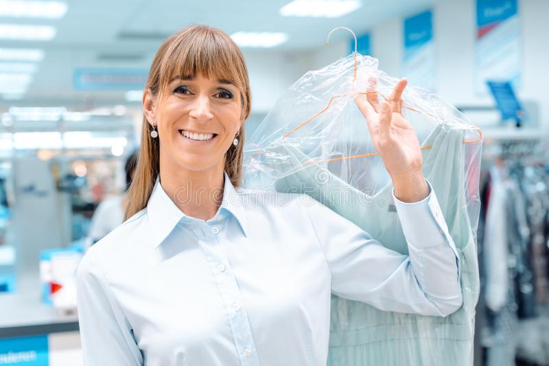Cliente della donna che ottiene i vestiti puliti indietro dalla pulizia del tessuto fotografia stock