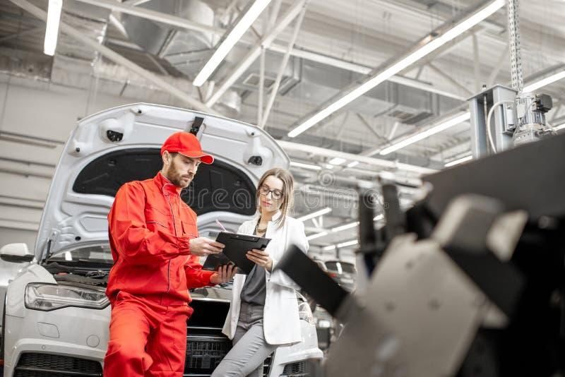 Cliente della donna con il meccanico al servizio dell'automobile fotografie stock libere da diritti