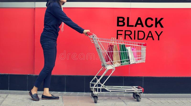 Cliente della donna, di Black Friday e sacchetto della spesa in un carrello immagine stock