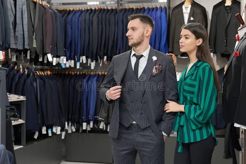 Cliente in deposito che sceglie abbigliamento, aiuto del commesso fotografia stock libera da diritti