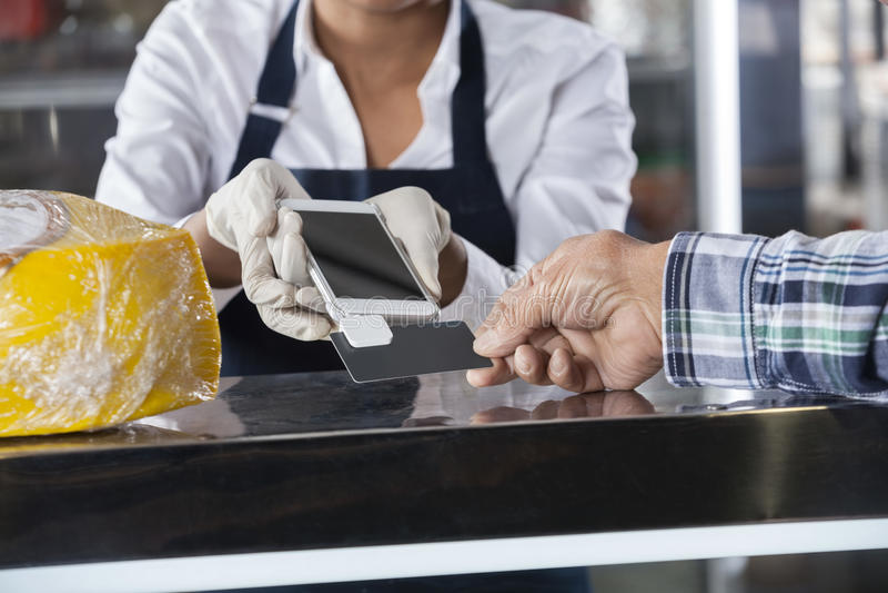Cliente di Accepting Payment From della venditora nel negozio del formaggio fotografie stock libere da diritti