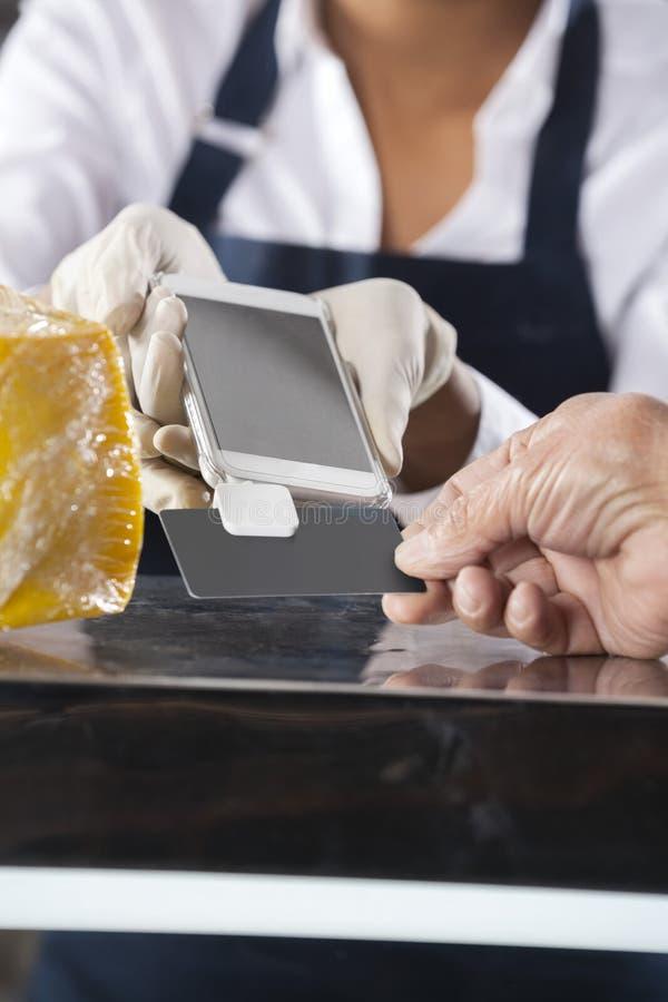 Cliente di Accepting Payment From della venditora nel negozio del formaggio immagini stock libere da diritti