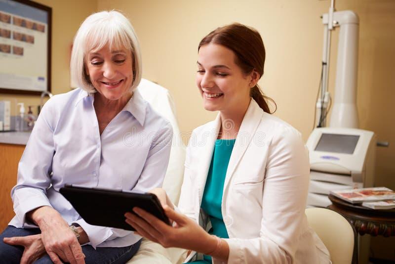 Cliente di Discussing Proceedure With del chirurgo cosmetico in ufficio fotografia stock