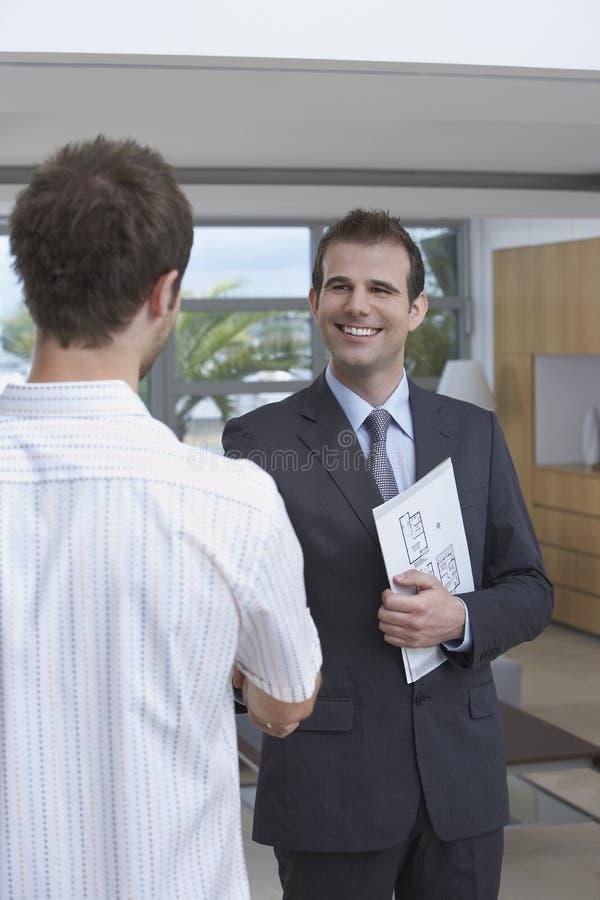 Cliente di Shaking Hands With dell'agente immobiliare all'interno fotografia stock