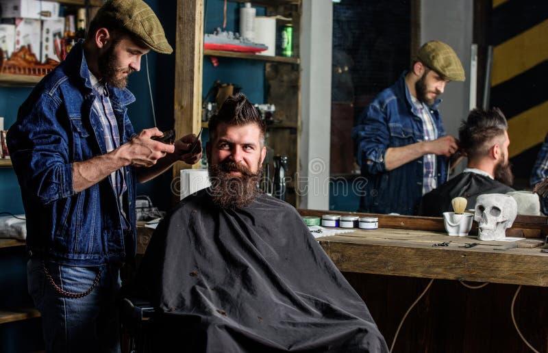 Cliente do barbeiro e do moderno com barba que verifica o corte de cabelo no espelho, fundo escuro O homem com barba explica o pe fotografia de stock