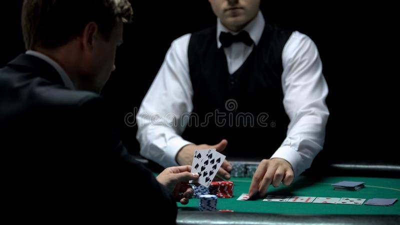Cliente do casino da virada que tem a combinação má no pôquer, vitórias fracas dos cartões da casa da mão fotografia de stock