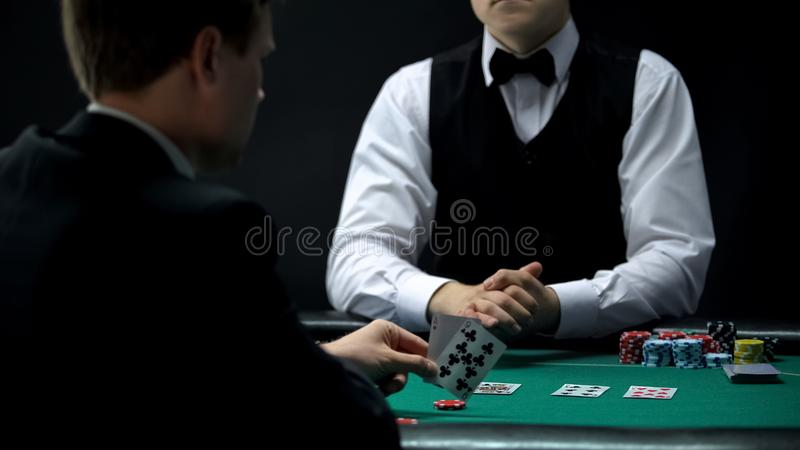 Cliente do casino que olha os cartões negociados pelo crouoier, possibilidade ganhar no jogo de pôquer imagem de stock