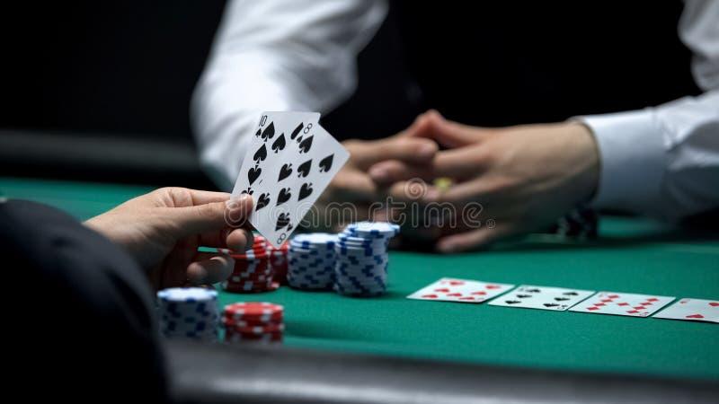 Cliente do casino que tem a combinação fraca da mão no pôquer que faz a aposta grande com as microplaquetas fotos de stock royalty free