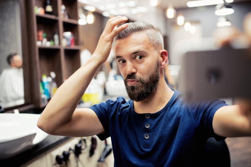 Cliente do homem do moderno na barbearia, fazendo as caras engraçadas ao tomar o seflie fotografia de stock