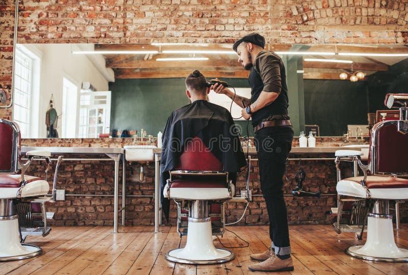 Cliente do serviço do barbeiro na barbearia foto de stock
