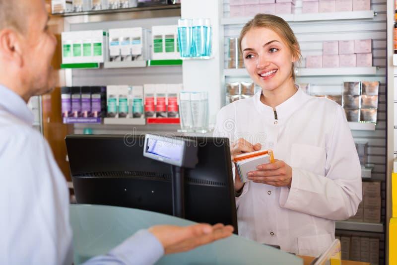 Cliente do serviço do farmacêutico na farmácia imagem de stock