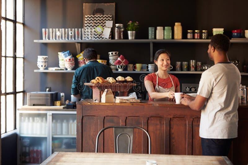 Cliente do serviço do pessoal na cafetaria ocupada foto de stock royalty free