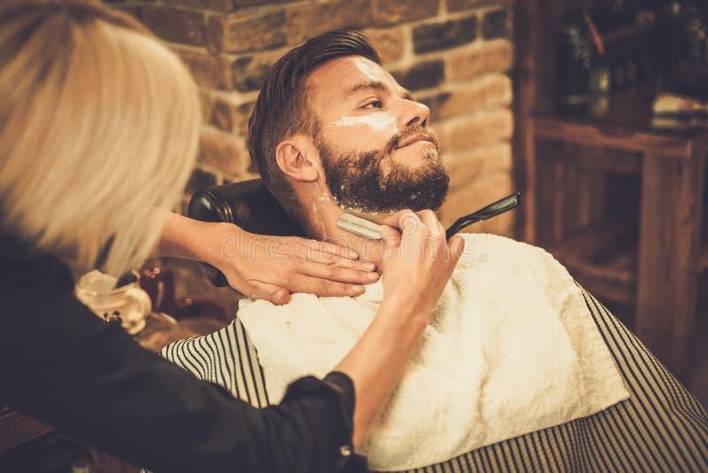 Cliente durante afeitar de la barba foto de archivo