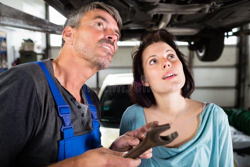 Cliente e mecânico que verificam defeitos no carro imagens de stock royalty free