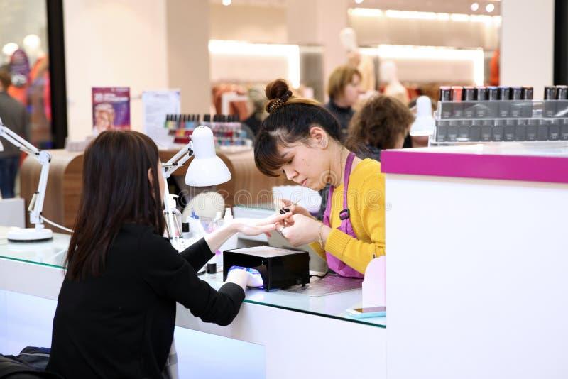 Cliente e o mestre do tratamento de mãos expresso no shopping fotos de stock royalty free