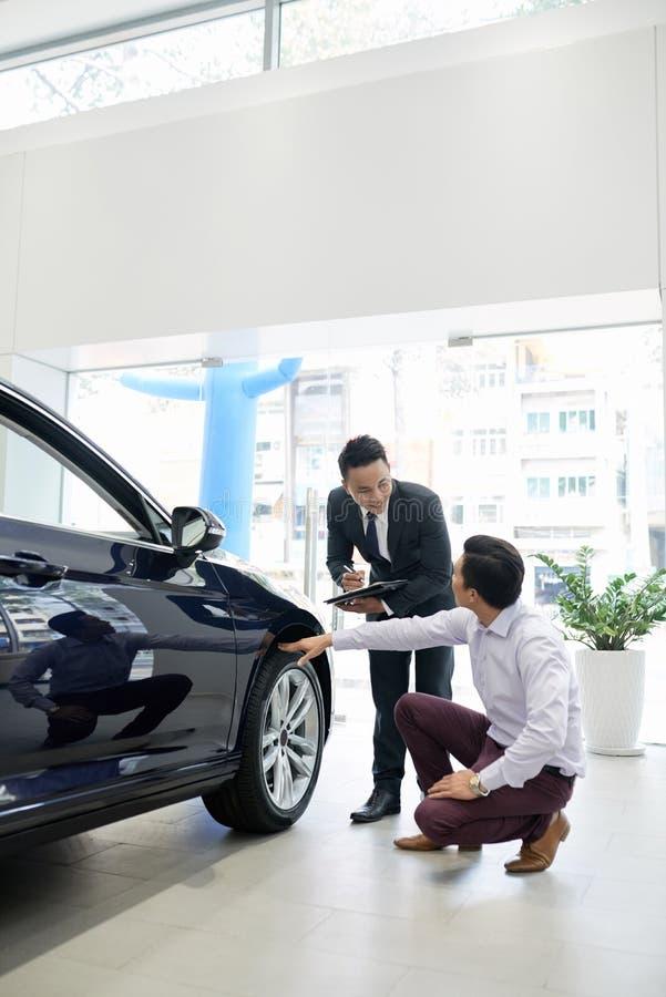 Cliente e vendedor que discutem pneus imagem de stock royalty free