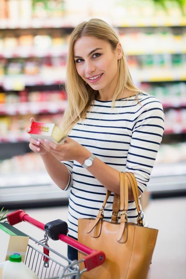 Cliente en el supermercado que celebra un producto y una sonrisa imagen de archivo