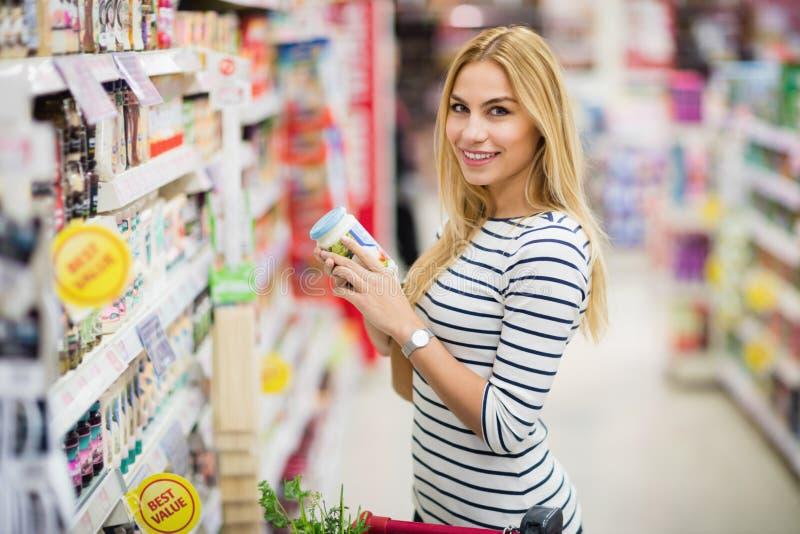 Cliente en el supermercado que elige un producto imagen de archivo