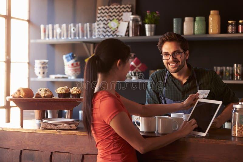 Cliente en la cafetería que paga usando lector de la tableta de Digitaces foto de archivo libre de regalías