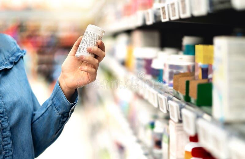 Cliente en la farmacia que sostiene la botella de la medicina Mujer que lee el texto de la etiqueta sobre la información médica o fotos de archivo libres de regalías