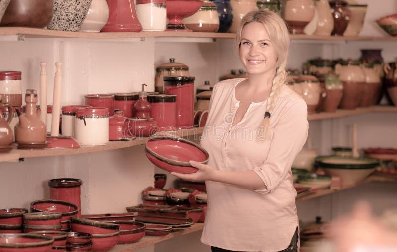 Cliente fêmea alegre que escolhe a louça vitrificada vermelho imagens de stock