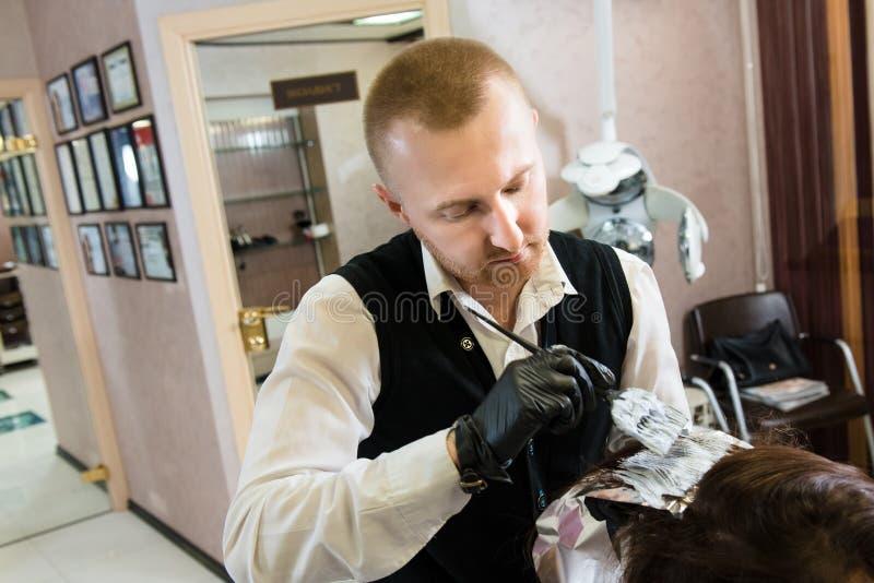 Cliente fêmea da cor masculina profissional do cabeleireiro no salão de beleza do projeto foto de stock royalty free