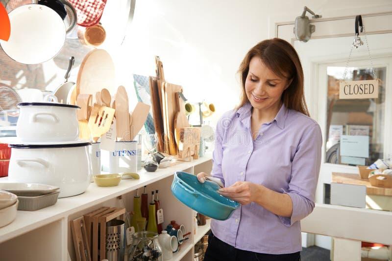 Cliente fêmea maduro que olha o prato no cozinheiro Shop foto de stock royalty free