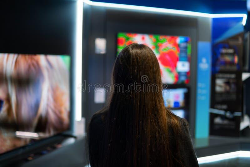 Cliente fêmea moderno esperto que escolhe grandes aparelhos de televisão imagens de stock royalty free